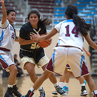 Chinle Wildcat Kalli Hunter (32) dribbles through three Ganado guards during the game in Ganado Tuesday.