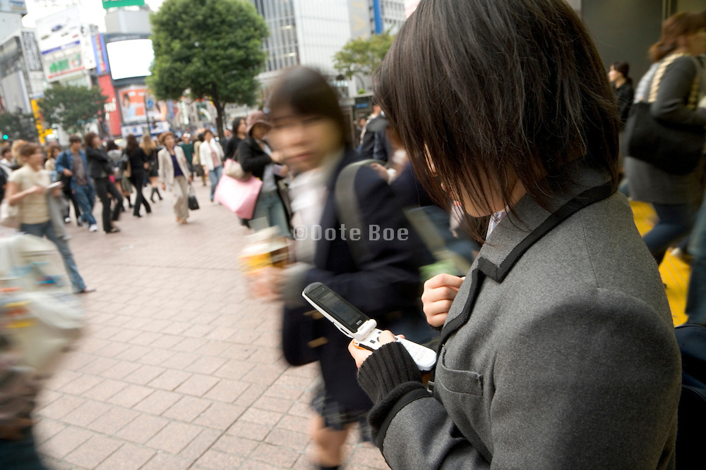 young girl in school uniform checking her cell phone Tokyo Japan