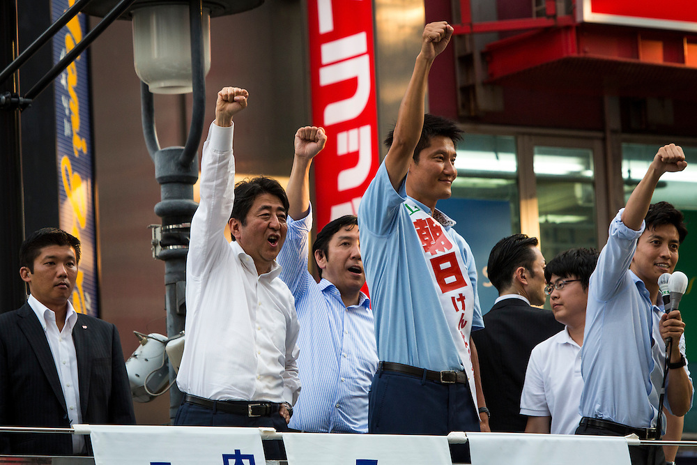 TOKYO, JAPAN - JULY 03 : Japanese Prime Minister Shinzo Abe, president of the ruling Liberal Democratic Party (LDP), and candidate Kentaro Asahi raises their fist to the supporters during the Upper House election campaign in Shibuya crossing, Tokyo prefecture, Japan, on July 3, 2016. (Photo by Richard Atrero de Guzman/ANADOLU AGENCY)