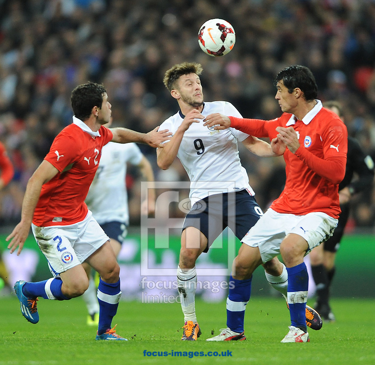 Picture by Daniel Hambury/Focus Images Ltd +44 7813 022858<br /> 15/11/2013<br /> Adam Lallana of England gets between Eugenio Mena and Marcos Gonzalez of Chile during the Friendly match at Wembley Stadium, London.