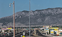 a freeway passes through downtown Albuquerque, New Mexico with traffic cam (camera) pole and Sandia Peak in the distance.