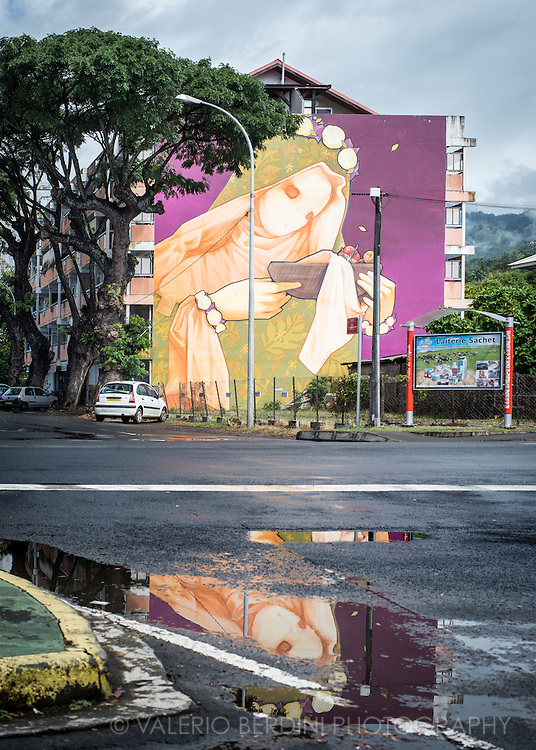 A large graffiti depicting the Virgin Mary, reflects in a puddle after a tropical storm in Papeete.