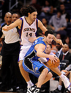 Dec. 09, 2012; Phoenix, AZ, USA; Orlando Magic guard J.J. Redick (7) is guarded by Phoenix Suns forward Luis Scola (14) in the second half at US Airways Center. The Magic defeated the Suns 98-90. Mandatory Credit: Jennifer Stewart-USA TODAY Sports.