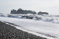 Waves crashing on a stoney beach with sea stacks out beyond the surf at Rialto Beach, Olympic National Park, Washington State.
