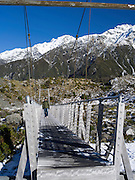 An Asian man walks across a suspension bridge on his way up the Hooker Valley Track, Aoraki/Mt. Cook National Park.