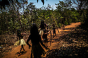 A group Xerente indigenous people walk from their village to a nearby river near Tocantinia, Brazil, Friday, October 2, 2015.  One nearly empty vastness some decades ago, the northern part of Goias state territory, Tocantins was the latest Brazilian state to be created,  27 years ago. Now, luring Brazilians with an abundance of natural resources, its indigenous heritage, an aura of sustainability, infrastructure and lower prices, the government vows that this solid investment package will make up the facade of a land of opportunity. And eventually attract qualified workforce to populate the area. Profiting from side publicity of two world events, Brazil aims at throwing some light on its developmental potential, and has already helped to transform the locally known national indigenous games in the first international event of this type. In some weeks thousands of indigenous athletes from 24 countries will flock to the arena to compete, share and showcase their faces to the world.  (Hilaea Media/ Dado Galdieri for the Wall Street Journal)
