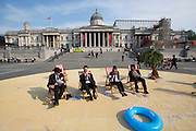 UNITED KINGDOM, London: 12 May 2016 Volunteers take part in a campaign to increase pressure on David Cameron and other world leaders to clamp down on tax dodging. Trafalgar Square was turned into a tropical 'tax haven' this morning as volunteers  dressed in business suits and bowler hats organised by Oxfam, ActionAid and Christian Aid. <br /> Rick Findler / Story Picture Agency
