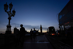 © Licensed to London News Pictures. 24/02/2017. London, UK. Commuters are seen in silhouette as the sun sets behind the Houses of Parliament. Photo credit : Stephen Chung/LNP