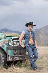 muscular cowboy in a sleeveless denim jacket by a truck
