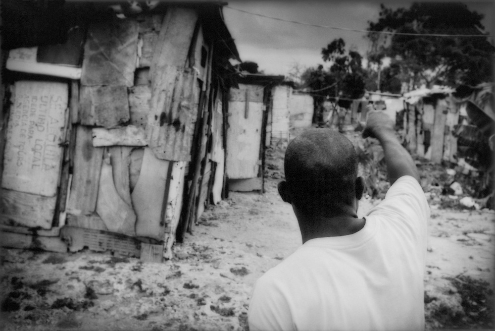 A resident of a squalid batey inhabited by Haitian construction workers points directions into the center, Boca Chica, Dominican Republic. The men from this batey work in the construction of new beachfront hotels and condominiums while their families live without access to water, healthcare, or education.