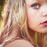 Close up of young woman with blonde hair looking into camera with evening sunlight