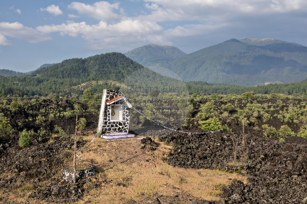 A shrine sits in a sea of dried lava rock in the remote village of San Juan Parangaricutiro, Michoacan, Mexico. This area was covered in an eight-year eruption of the Paricutin volcano which consumed two villages in 1943 and covered the region in lava and ash.