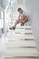 Mid-adult man sitting on stairs tying shoes