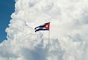 A Cuban flag flies against a backdrop of large cloud formations at Marina Marlin, near playa Ancon, Cuba, on Thursday July 3, 2008.