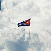A Cuban flag flies against a backdrop of large cloud formations at Marina Marlin, near playa Ancon, Cuba, on Thursday July 3, 2008.