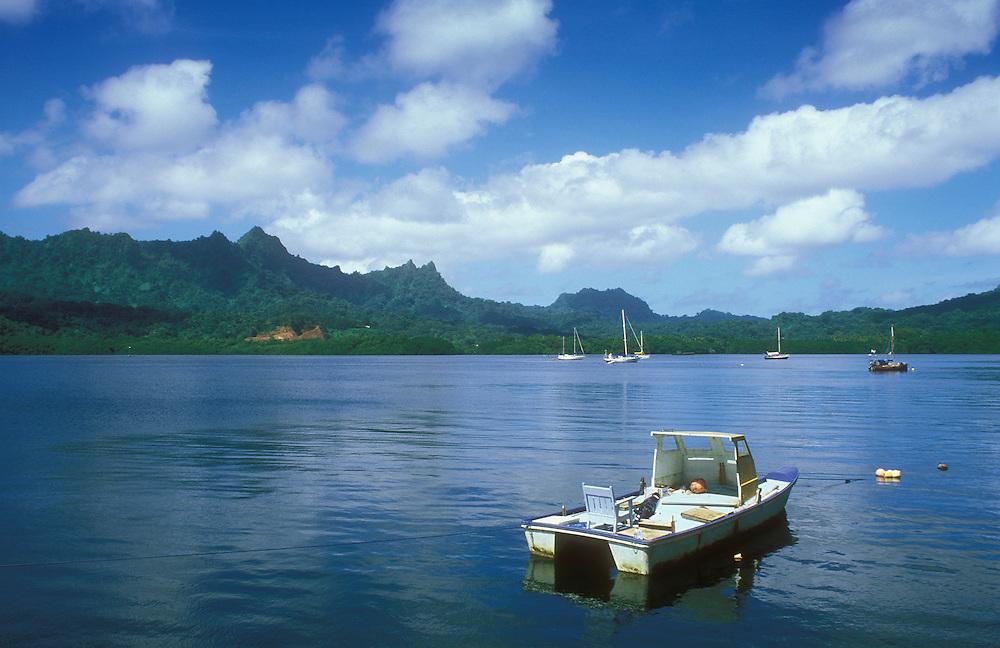 Boats in Lelu Harbor and view to Sleeping Lady mountain ridge profile; Kosrae, Micronesia.