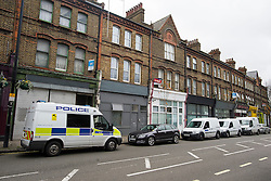 © Licensed to London News Pictures. 16/11/2015. London, UK. Police and forensics vehicles outside a property (white front) on Harrow Road , north west London where a man in his 30's was found dead at the scene by paramedics. A 24-year-old woman was arrested at the scene on suspicion of murder . Photo credit: Ben Cawthra/LNP