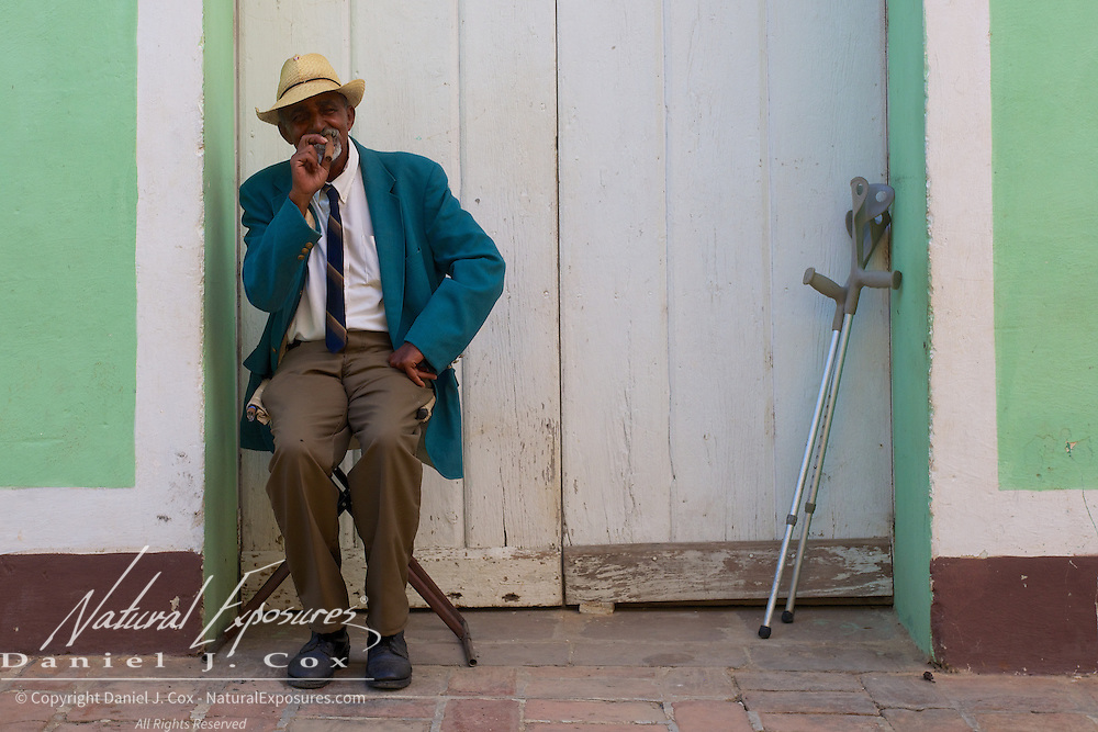 An old man smokes is cigar on the streets of Trinidad, Cuba.