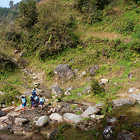 A group of students crossing a small river to their way to school, somewhere between Golphu Bhanjyang and Kutumsang.