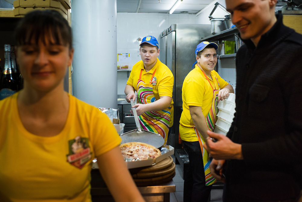 Veteran Artyom Rudenko, center-left, places a pizza in a box as fellow veteran Mikhail Yora, center-right, cleans up the kitchen at Veterano Pizza on January 24, 2016 in Kiev, Ukraine. At left and right are two other, non-veteran employees: Anna Krause, and Dimitrii Terechshenko. (Pete Kiehart for The New York Times)