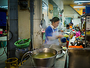 24 AUGUST 2018 - GEORGE TOWN, PENANG, MALAYSIA: A woman makes noodle soup in a restaurant across the street from Chowrasta Market in central George Town. Chowrasta Market was originally built in 1890 and is the older of two traditional markets in George Town. The original building was torn down and replaced with a modern building in 1961 and has been renovated several times since.     PHOTO BY JACK KURTZ