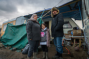 A family from Iraqi Kurdistan stand outside a caravan where they lived for several months in the Calais refugee camp known as 'the jungle'. The caravan was donated to the family by British based organisation Jungle Canopy.