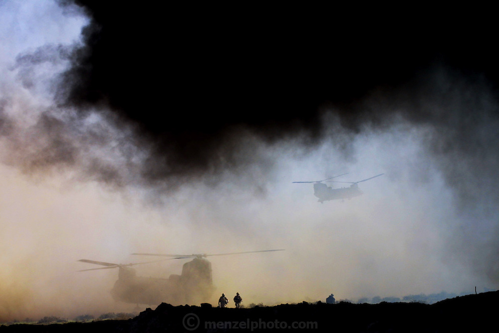 US Army helicopters landing near burning oil wells in Iraq's Rumaila Oil Field, in southern Iraq. The wells were set on fire with explosives placed by retreating Iraqi troops when the US and UK invasion began. Seven or eight wells were set ablaze but at least one other was detonated but did not ignite. The Rumaila field is one of Iraq's biggest oil fields with five billion barrels in reserve. Many of the wells are 10,000 feet deep and produce huge volumes of oil and gas under tremendous pressure, which makes capping them very difficult and dangerous. Rumaila is also spelled Rumeilah.