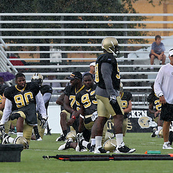 August 9, 2011; Metairie, LA, USA; New Orleans Saints head coach Sean Payton walks by players stretching  in a rain storm during training camp practice at the New Orleans Saints practice facility. Mandatory Credit: Derick E. Hingle