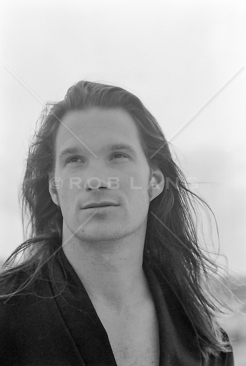 portrait of a man with very long hair outdoors