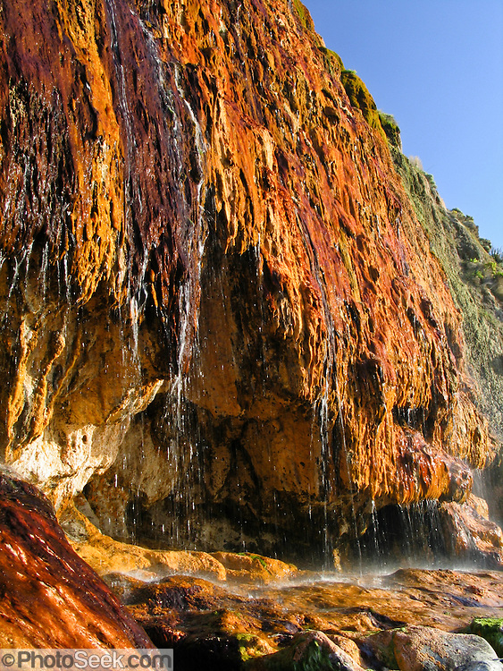 Rainbow Falls, Cape Otway, Great Otway National Park, Victoria, Australia. Rainbow Falls flow from a spring in the dune limestone, forming colorful orange, red, and brown limestone deposits as it flows over the rocks directly into the tideline of the Indian Ocean (or Southern Ocean according to Australian geographers). In direct afternoon sunlight, water flowing over the escarpment forms a beautiful rainbow. Walk to Rainbow Falls from Bimbi Park campground or from Cape Otway Lightstation. The Great Ocean Road (B100) is a 243-km road along the southeast coast of Australia between Torquay and Warrnambool, in the state of Victoria. Dedicated to casualties of World War I, the Great Ocean Road was built by returned soldiers between 1919 and 1932 and is the world's largest war memorial. Photo was captured with a polarizing filter to reduce reflections.