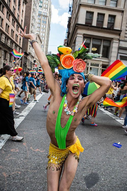 New York, NY - 25 June 2017. New York City Heritage of Pride March filled Fifth Avenue for hours with groups from the LGBT community and it's supporters. An exuberant man in a minimal costume topped by a Carmen Miranda-inspired headpiece.