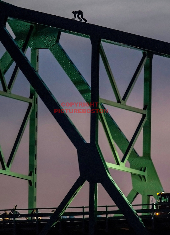 06/10/15-Boston,MA. A man, threatening to jump from the Tobin Bridge, is seen climbing the bridge this evening as police at bottom try to talk him down.