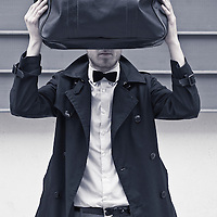 A young man wearing a bow tie and a black raincoat holding a black bag up infront of his face