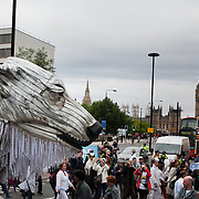 Aurora pass Westminster Bridge, Big Ben and Parliament. The giant polar bear puppet Aurora made by Greenpeace walked the streets of London in defence of the Arctic as part of a Greenpeace global day of action. The parade,part performance part protest, was to highlight the melting ice caps and the increasing and potentially devastating oil drilling in the arctic sea. Shell is one of the companies drilling and the march through London ended up outside Shell London HQ to draw attention to their oil business in the arctic. Aurora, the biggest polar bear in the world represents all endangered species in arctic.