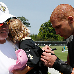 Jul 26, 2013; Metairie, LA, USA; New Orleans Saints tight end Jimmy Graham (80) signs an autograph for three year old Lucy Loomis as she is held by general manager Mickey Loomis following the end of the first day of training camp at the team facility. Mandatory Credit: Derick E. Hingle-USA TODAY Sports