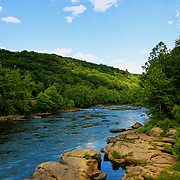 """""""Rocks on the Yough""""<br /> <br /> A lovely summertime view of the Youghiogheny River in Ohiopyle.<br /> Beautiful blue water, lush woodlands, and water smoothed rock formations make a fantastic  scene!!<br /> <br /> Laurel Highlands Area of Pennsylvania by Rachel Cohen"""
