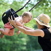 A fourteen month old baby girl enjoys playing on the swing with her mother in a playground setting during play. Photo Tim Clayton