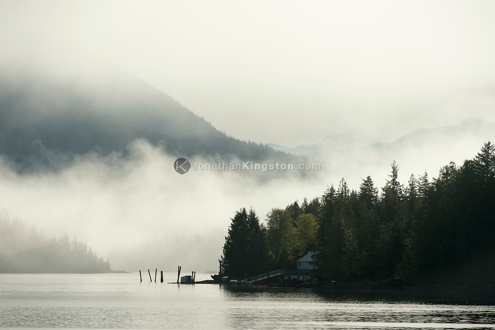 Fog lifts behind a house with a dock on the Inside Passage of BC.