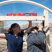 Dibe Yazhi Habitiin Community School seventh grade student Shandiin White, left, uses a level to ensure a piece of wood is straight as Jesse Jim, a 4H tribal extension agent with New Mexico State University constructs a door frame on one end of the hoop house Thursday, March 28 in Crownpoint.