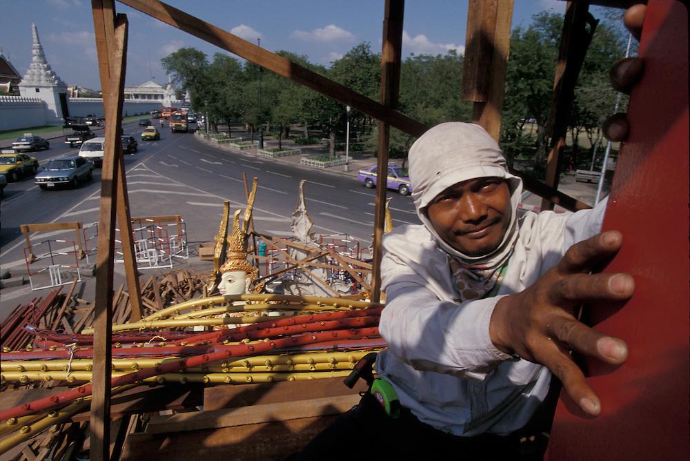 Thailand, Bangkok, Workman atop monument near Grand Palace