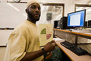 "Woodbourne Correctional Facility inmate and Bard College student Abdullah Kamau Sankofa studies in the computer room. He has been sentenced to 18 years in prison at the age of 17. He graduated from Bard College with fellow inmate Carlos Rosario in May 2010. (Book: The Coming of the French Revolution)..Story: The Bard Prison Initiative.Former inmate Carlos Rosario, 35-year-old husband and father of four, was released from Woodbourne Correctional Facility after serving more than 12 years for armed robbery. Rosado is one of the students participating in the Bard Prison Initiative, a privately-funded program that offers inmates at five New York State prisons the opportunity to work toward a college degree from Bard College. The program, which is the brainchild of alumnus Max Kenner, is competitive, accepting only 15 new students at each facility every other year. .Carlos Rosario received the Bachelor of Arts degree in social studies from the prestigious College Saturday, just a few days after his release. He had been working on it for the last six years. His senior thesis was titled ""The Diet of Punishment: Prison Food and Penal Practice in the Post-Rehabilitative Era,"".Rosado is credited with developing a garden in one of the few green spaces inside the otherwise cement-heavy prison. In the two years since the garden's foundation, it has provided some of the only access the prison's 800 inmates have to fresh vegetables and fruit...Rosario now works for a recycling company in Poughkeepsie, N.Y...Photo © Stefan Falke"
