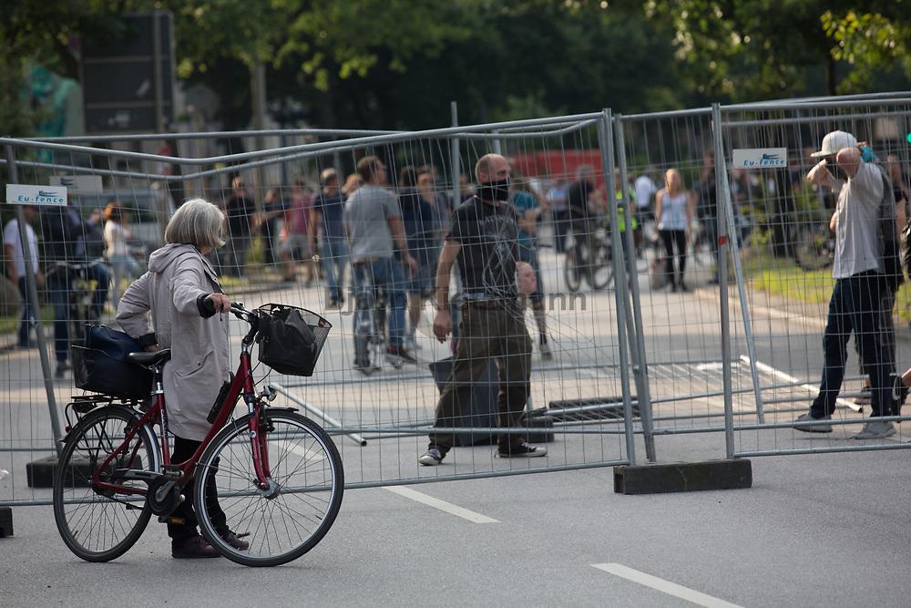 Hamburg, Germany - 07.07.2017<br /> <br /> A cyclist watched barricade construction during the Anti G20 protests in Hamburg.<br /> <br /> Eine Radfahrerin beobachtet Barrikadenbau bei den Anti G20-Proteste in Hamburg.<br /> <br /> Photo: Bjoern Kietzmann