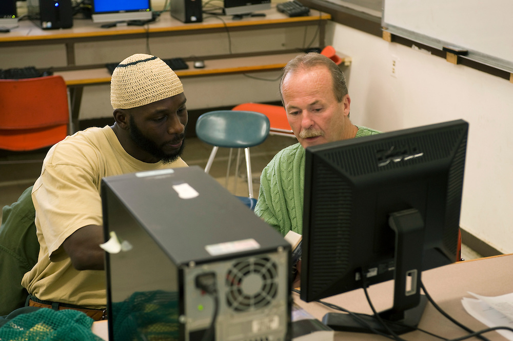 "Woodbourne Correctional Facility inmate and Bard College student Abdullah Kamau Sankofa (left) studies in the computer room. He has been sentenced to 18 years in prison at the age of 17. He graduated from Bard College with fellow inmate Carlos Rosario in May 2010. (Book: The Coming of the French Revolution) Bill Doane (55) is one of his mentors...Story: The Bard Prison Initiative.Former inmate Carlos Rosario, 35-year-old husband and father of four, was released from Woodbourne Correctional Facility after serving more than 12 years for armed robbery. Rosado is one of the students participating in the Bard Prison Initiative, a privately-funded program that offers inmates at five New York State prisons the opportunity to work toward a college degree from Bard College. The program, which is the brainchild of alumnus Max Kenner, is competitive, accepting only 15 new students at each facility every other year. .Carlos Rosario received the Bachelor of Arts degree in social studies from the prestigious College Saturday, just a few days after his release. He had been working on it for the last six years. His senior thesis was titled ""The Diet of Punishment: Prison Food and Penal Practice in the Post-Rehabilitative Era,"".Rosado is credited with developing a garden in one of the few green spaces inside the otherwise cement-heavy prison. In the two years since the garden's foundation, it has provided some of the only access the prison's 800 inmates have to fresh vegetables and fruit...Rosario now works for a recycling company in Poughkeepsie, N.Y...Photo © Stefan Falke"