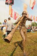 A strange man covered in mud blowing a didgeridoo, Glastonbury 2005