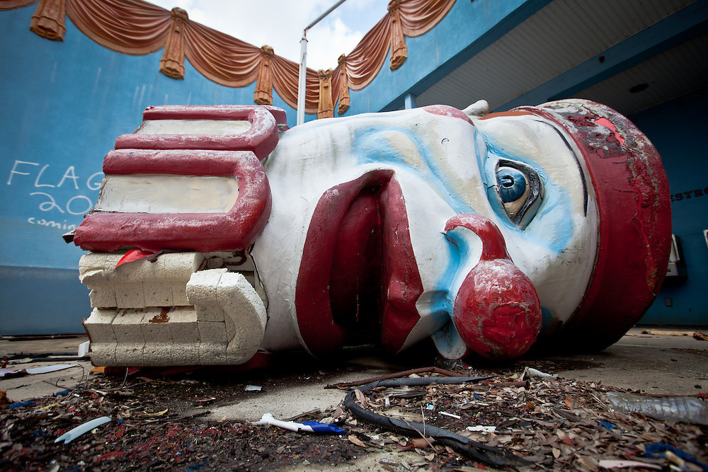 Broken clown head next to abandoned buildings at Six Flags in New Orleans.  Six Flags New Orleans amusement park in Eastern New Orleans, Louisiana, closed since Hurricane Katrina  in 2005 remains in a sate of ruin. The remains of Six Flags amusement park are on low lying land owned by the city of New Orleans and have not be redeveloped since Katrina.