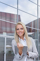 Portrait of happy businesswoman holding digital tablet against office building