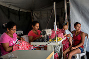 2016/07/27 – Portoviejo, Ecuador: Miriam Zambrano (in the centre), 37, works on her sawing machine on a tent at the shelter located on the old airport, Portoviejo, Ecuador, with the help of another lady, while her daughter-in-law takes care of Miriam's grandson, 27th July 2016. Miriam managed to recover her sawing machine from the wreckage, and kept working as a dressmaker in order to sustain her six children, one daughter-in-law and one grandson. She is happy to be in the shelter and hopes that eventually she will get a house from the Government. (Eduardo Leal)