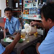 Vietnamese men enjoy lunch on a street corner in Ho Chi Minh City, Vietnam. 3rd March 2012. Photo Tim Clayton