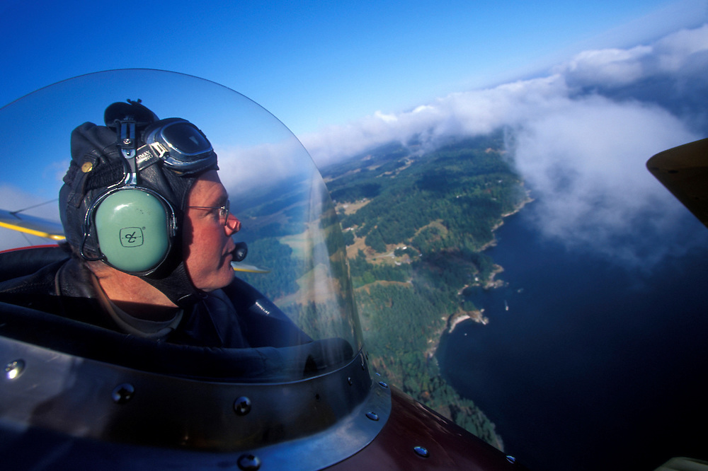 USA, Washington, Rod Magner pilots TravelAir Biplane over Orcas Island above morning fog and clouds