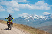 Little boy riding dirt bike on Trapper Creek Road along the Lower Goose Creek Reservoir with view of snow capped mountains beyond during spring near Oakley, Idaho.